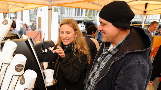Rep., Melanie Holdway, left, assists Chris Narcio brew his free cup of coffee at the Keurig Buzz Event/3D Chalk Drawing in Pioneer Square in Portland, Ore., Thursday Nov., 1, 2012. (Photo by Greg Wahl-Stephens/AP Images for Keurig Incorporated)