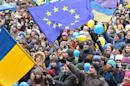 Students wave Ukrainian and European Union flags as they shout slogans during a rally of the opposition in the western Ukrainian city of Lviv on December 5, 2013