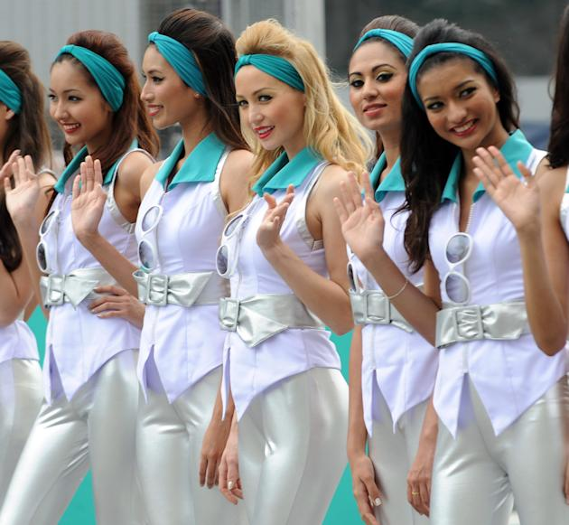 Grid girls pose for photographers during the drivers' grid introductory ceremony prior to the start of Formula One's Malaysian Grand Prix at the Sepang International Circuit in Sepang on March 25, 201