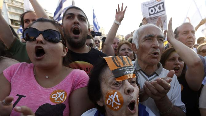 """Demonstrators wear """"No"""" stickers (Oxi in Greek) during an anti-austerity rally in Athens"""