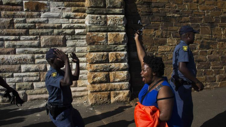 A woman reacts as she arrives at Union Buildings in Pretoria, where the body of Nelson Mandela is lying in state