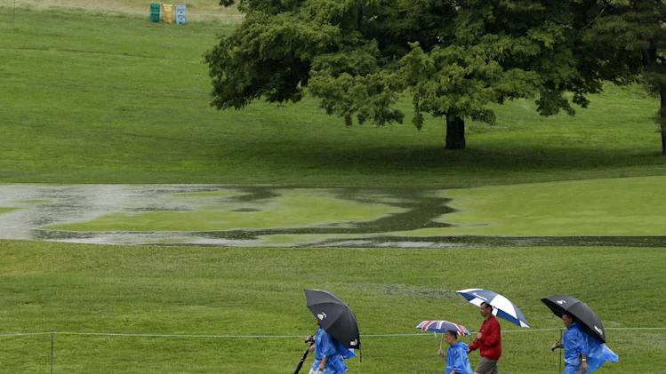 Golf fans walk down the 16th fairway as rain falls at Merion Golf  Club, in Ardmore, Pa., Monday, June 10, 2013. The 2013 U.S. Open championship will be played here June 13-16. (AP Photo/Gene Puskar)