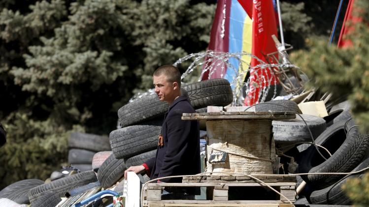 Pro-Russian protester stands guard at a barricade near the seized office of the SBU state security service in Luhansk