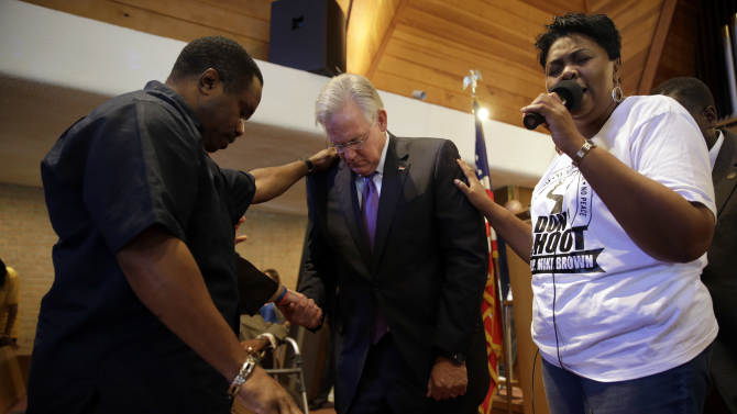 """Missouri Gov. Jay Nixon, center, prays during a meeting of clergy and community members held to discuss law enforcement's response to demonstrations over the killing of Michael Brown, Thursday, Aug. 14, 2014, in Florissant, Mo. Nixon says """"operational shifts"""" are ahead for law enforcement in the St. Louis suburb where a police officer fatally shot an unarmed black teenager. (AP Photo/Jeff Roberson)"""