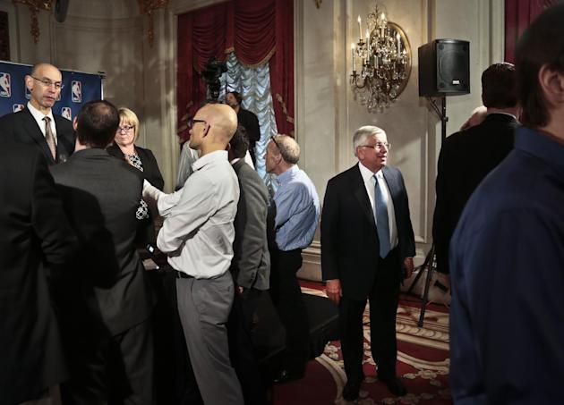 NBA Deputy Commissioner Adam Silver, far left, speaks with reporters as NBA Commissioner David Stern, third from right, leaves after a press conference at the NBA board of governors meeting, Wednesday