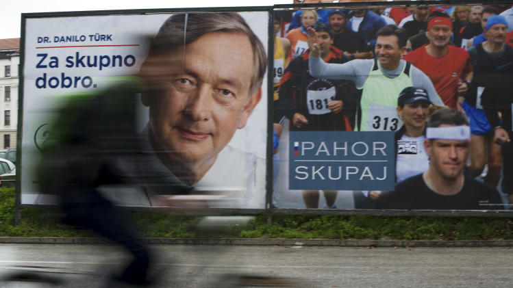 A cyclist rides past electoral posters of president incumbent, Danilo Turk, left and former prime minister Borut Pahor in Ljubljana, Slovenia, Friday, Nov. 30, 2012. Thousands protested against the government in Slovenia on Friday, as tensions soared ahead of this weekend's presidential runoff in the small and economically struggling EU member state that is in danger of needing an international bailout.  (AP Photo/Matej Leskovsek)