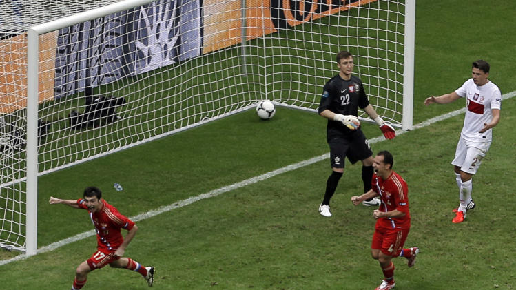 Russia's Alan Dzagoyev, left, celebrates scoring the opening goal during the Euro 2012 soccer championship Group A match between Poland and Russia in Warsaw, Poland, Tuesday, June 12, 2012. (AP Photo/Gero Breloer)