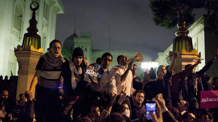 Egyptian protesters chant anti Muslim Brotherhood slogans during a demonstration in front of the main gate of the presidential palace, background, in Cairo, Egypt, Tuesday, Dec. 4, 2012. A protest by tens of thousands of Egyptians outside the presidential palace in Cairo turned violent on Tuesday as tensions grew over Islamist President Mohammed Morsi's seizure of nearly unrestricted powers and a draft constitution hurriedly adopted by his allies. (AP Photo/Nasser Nasser)