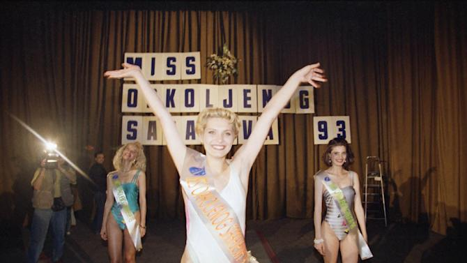 "FILE - In this May 29, 1993 file photo, Imela Nogic, 17, reacts after winning the Miss Besieged Sarajevo 93 contest in Sarajevo. Hearts melted worldwide when instead of tearfully wishing ""world peace"" as she was crowned Miss Besieged Sarajevo, 17 year-old Inela Nogic folded out a banner that read: ""Don't let them kill us."" (AP Photo/Jerome Delay, File)"