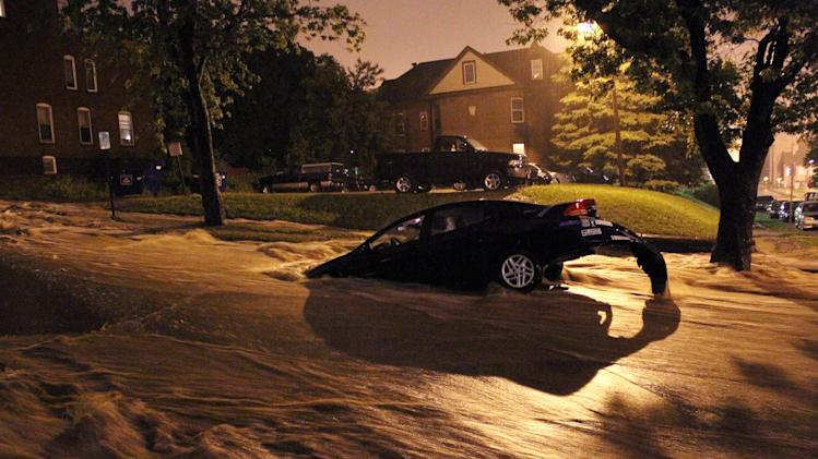 A car is stranded in floodwaters rushing down a hillside in Duluth, Minn., early Wednesday, June 20, 2012. Hours of torrential rainfall have sparked major flooding across the city and along the North Shore of Lake Superior, with some homes being evacuated due to rising water. (AP Photo/The Duluth News-Tribune, Andrew Krueger)