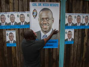 Posters of opposition leader Kizza Besigye are put …
