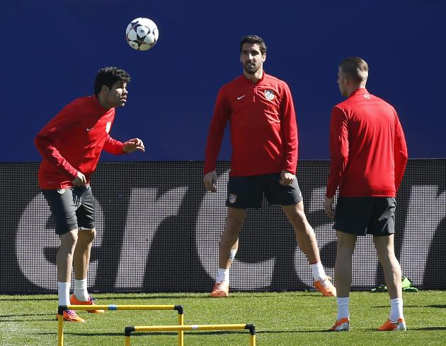 Atletico Madrid's Diego Costa heads the ball next to teammates Raul Garcia and Toby Alderweireld during a training session at the Vicente Calderon stadium in Madrid
