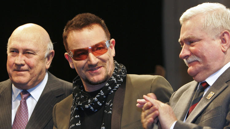FILE - This is a Friday, Dec. 12, 2008 file photo of Irish singer and activist Bono, center, as neposes with 1993 Nobel Peace Laureate F. W. de Klerk, left, and 1983 Nobel Peace Laureate Lech Walesa after Bono was awarded with the Peace Summit Award during the 9th Summit of Nobel Peace Laureates, in Paris. (AP Photo/Jacques Brinon, File)