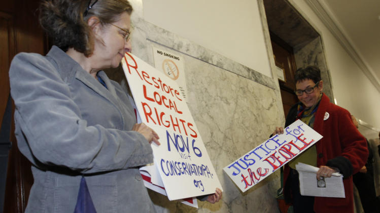 Cynthis Walter, left, with the Westmoreland Marcellus Citizens Group holds her sign with another woman after they left the Pennsylvania state Supreme Courtroom in Pittsburgh where the court was hearing arguments from seven municipalities challenging portions of a new law that regulates natural gas exploration on  Wednesday, Oct. 17, 2012. (AP Photo/Keith Srakocic)