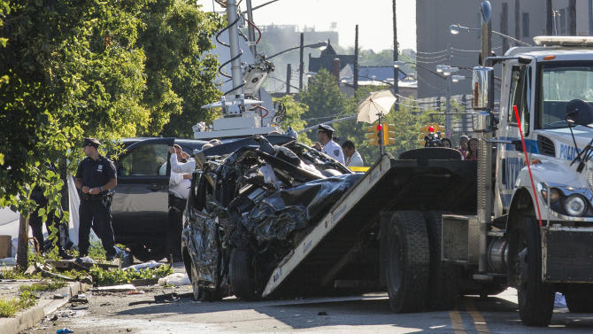 Authorities clear an automobile involved in a single-vehicle crash that took the lives of five people, including two children, near the Van Wyck Expressway, Sunday, July 22, 2012, in the Queens borough of New York. A New York Fire Department spokesperson stated that one person was critically injured and two others suffered serious injuries in the crash that occurred at 3:17 a.m., all of whom were taken to Jamaica Hospital. (AP Photo/John Minchillo)