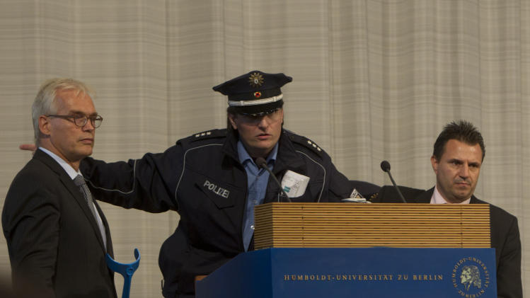 A police officer calls for an immediate evacuation of the main hall of the Humboldt University minutes prior to a speech of Turkish President Abdullah Gul in Berlin, Monday, Sept. 19, 2011. Berlin police cleared the university where Turkish President Abdullah Gul was due to speak after a German news agency reported a bomb threat. (AP Photo/Markus Schreiber)