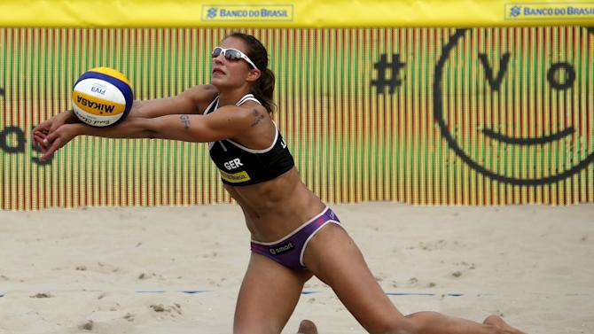 Laboureur of Germany saves a ball against Maria Antonelli and Juliana Felisberta of Brazil during their Rio Open women's beach volleyball match on Copacabana beach in Rio de Janeiro