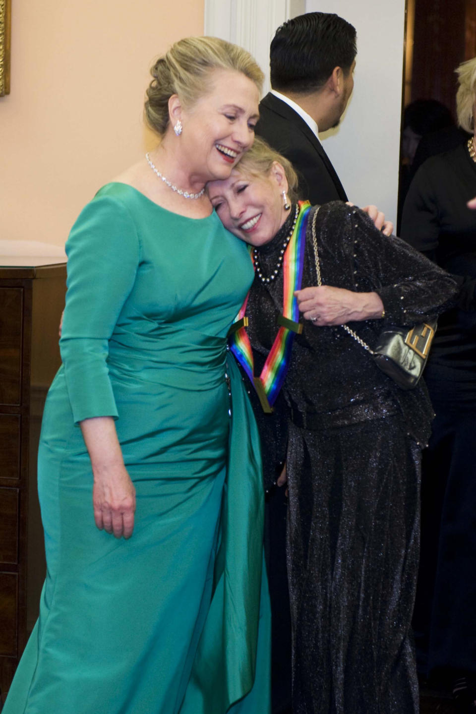 Secretary of State Hillary Rodham Clinton, left, hugs 2012 Kennedy Center Honoree Natalia Makarova at the end of the State Department Dinner for the Kennedy Center Honors gala Saturday, Dec. 1, 2012 at the State Department in Washington. (AP Photo/Kevin Wolf)