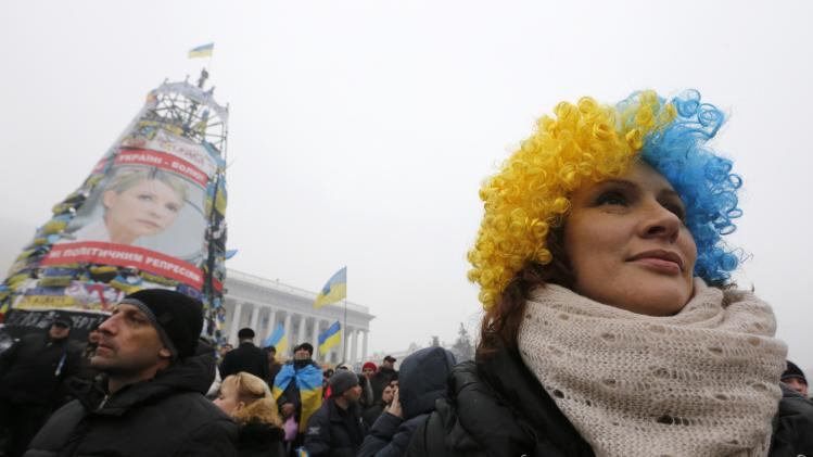 Pro-European integration protesters hold a rally as a poster of jailed opposition leader Tymoshenko at Independence Square is pictured in the background in central Kiev