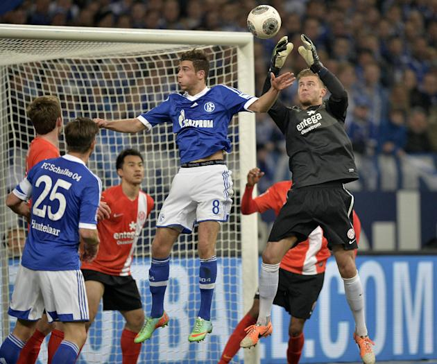 Schalke's Leon Goretzka, center, and Mainz goalkeeper Loris Karius, right, challenge for the ball during the German Bundesliga soccer match between FC Schalke 04 and FSV Mainz 05 in Gelsenkirchen,