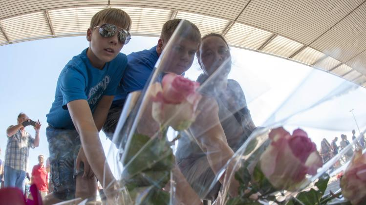 People leave flowers while paying their respects at Schiphol Airport during a national day of mourning for the victims of the downed flight MH17