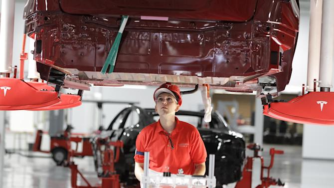 A worker works on the Tesla Model S at the Tesla factory in Fremont, Calif., Friday, June 22, 2012. The first Model S sedan car will be rolling off the assembly line on Friday.  (AP Photo/Paul Sakuma)