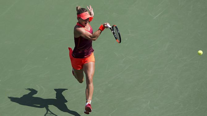 Halep of Romania hits the ball to Erakovic of New Zealand in their first round match at the U.S. Open Championships tennis tournament in New York