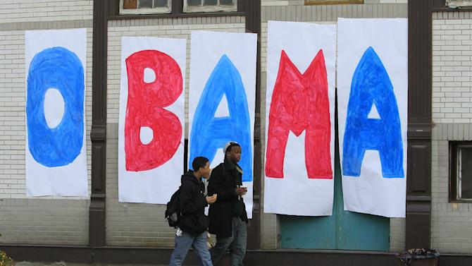 Jaylen Williams, left, and Sean Tyus walk past a home made Obama sign on their way to school, Wednesday, Nov. 7, 2012, in the Over-the-Rhine neighborhood of downtown Cincinnati. President Barack Obama captured a second White House term on Tuesday over the  challenge by Republican Mitt Romney. (AP Photo/Al Behrman)