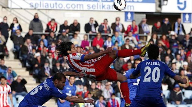 Atletico Madrid's Radamel Falcao (C) tries to kick the ball between Getafe's Albert Lopo (L) and Juan Valera (Reuters)