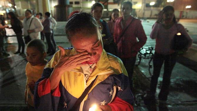A woman holds a candle as she reacts during a vigil in support of Venezuela's President Hugo Chavez in Caracas, Venezuela, Thursday, Dec. 13, 2012. Chavez is recovering favorably despite suffering complications during cancer surgery in Cuba, his vice president Nicolas Maduro said Thursday amid uncertainty over the Venezuelan leader's health crisis and the country's political future. (AP Photo/Fernando Llano)
