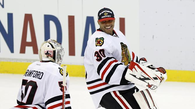 Chicago Blackhawks goalie Ray Emery (30) jokes with goalie Corey Crawford (50) after a 2-1 win over the Detroit Red Wings in overtime of an NHL hockey game on Sunday, March 3, 2013, in Detroit. (AP Photo/Duane Burleson)