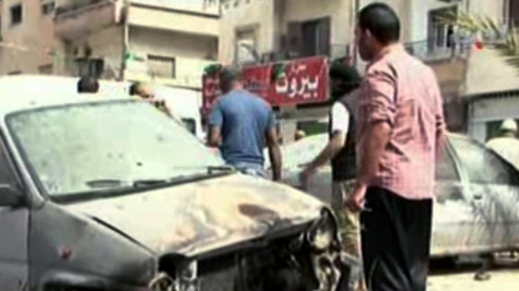 In this image made from video provided by APTN, Libyan men look at a damaged car at the site of a car bomb explosion in Benghazi, Libya, Monday, May 13, 2013. A car bomb exploded Monday near a hospital in the eastern Libyan city of Benghazi, killing many, officials said, in one of the biggest attacks since the end of the civil war that ousted former dictator Moammar Gadhafi. (AP Photo/APTN, Al Ahrar)