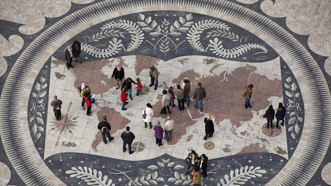 In this photo taken Dec. 26 2012, people look at a map of the world in Lisbon's Belem neighborhood at the Padrao dos Descobrimentos, or Monument to the Discoveries, that celebrate's Portugal's 15th and 16th century Age of Discovery. The map decorates the center of a marble wind rose offered to Portugal by South Africa. (AP Photo/Armando Franca)