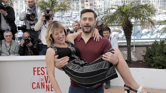 Director Valeria Bruni Tedeschi is carried by actor Filippo Timi during a photo call for the film Un Chateau en Italie at the 66th international film festival, in Cannes, southern France, Tuesday, May 21, 2013. (AP Photo/Lionel Cironneau)