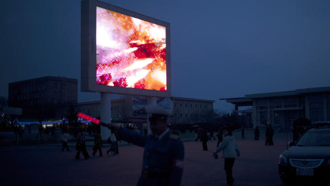 A traffic policeman directs cars while video on a screen shows rockets being fired at dusk in Pyongyang, North Korea, Wednesday, April 17, 2013. (AP Photo/Alexander F. Yuan)