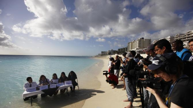 Environmental activists from 350.org, left, demonstrate before the cameras of journalists during the United Nations Climate Change Conference in Cancun, Mexico, Thursday Dec. 9, 2010.  (AP Photo/Eduardo Verdugo)