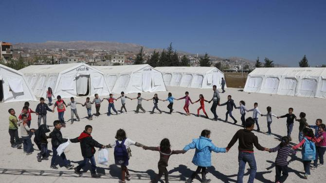 Syrian refugee children join hands as they play at a makeshift school in Zahle in the Bekaa valley