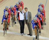 Sebastian Coe (C-R), Chairman of London 2012, and British Cycling Performance Director Dave Brailsford pose for photo as the British Track Cycling Team ride past them in the newly opened 2012 Olympic Velodrome in Stratford, east London, in February