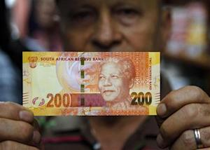 """A shop owner shows off South Africa's new banknotes, which features an image of former president Nelson Mandela on the front and images of the country's """"Big Five"""" wild animals on the reverse, as they go into official circulation in Pretoria"""
