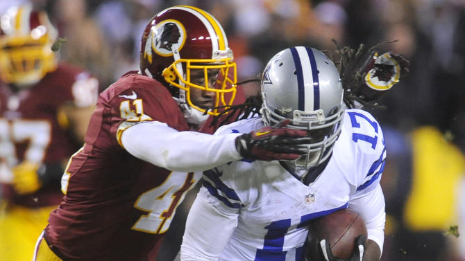Washington Redskins free safety Madieu Williams (41) tackles Dallas Cowboys wide receiver Dwayne Harris (17) during the first half of an NFL football game Sunday, Dec. 30, 2012, in Landover, Md. (AP Photo/Richard Lipski)