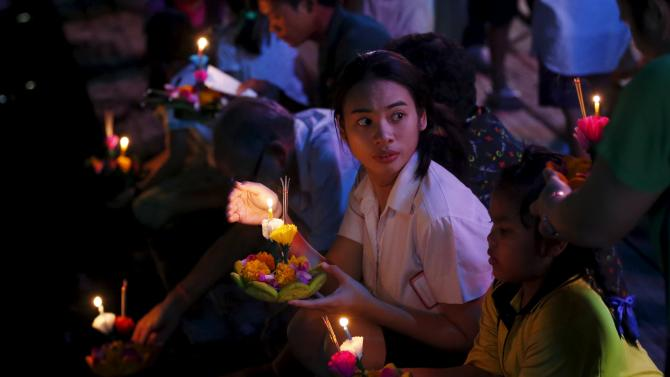 People pray before casting a krathong into a canal during the Loy Krathong festival in Nonthaburi province
