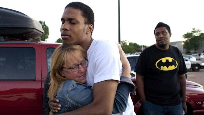 "FILE - In this Friday, July 20, 2012 file photo, Judy Goos, left, hugs her daughter's friend, Isaiah Bow, 20, an eyewitnesses, as Terrell Wallin, 20, right, looks on, outside Gateway High School where witnesses were brought for questioning after a gunman opened fire at the midnight premiere of the ""Dark Knight Rises"" movie in Aurora, Colo. After fleeing the theater, Bow returned to find his girlfriend who turned out to be safe. ""Very stupid I know, But I didn't want to leave her in there,"" says Bow. (AP Photo/Barry Gutierrez)"
