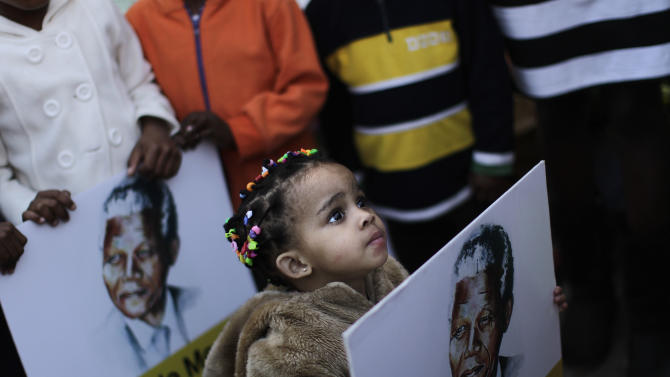 A South African girl holds a poster showing former South African President Nelson Mandela, while her family and other well wishers gather at the entrance to the Mediclinic Heart Hospital where former South African President Nelson Mandela is being treated in Pretoria, South Africa Friday, June 28, 2013. Members of Nelson Mandela's family as well as South African Cabinet ministers have visited the hospital on Friday where the 94-year-old former president is critically ill. (AP Photo/Muhammed Muheisen)
