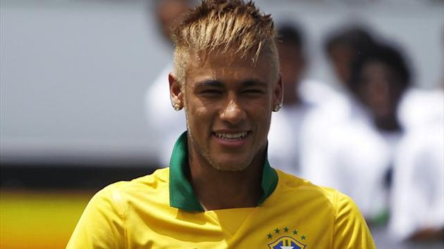 Brazil's national soccer player Neymar gestures as he wears the new team jersey during its presentation at the Copacabana beach in Rio de Janeiro January 31, 2013 (Reuters)