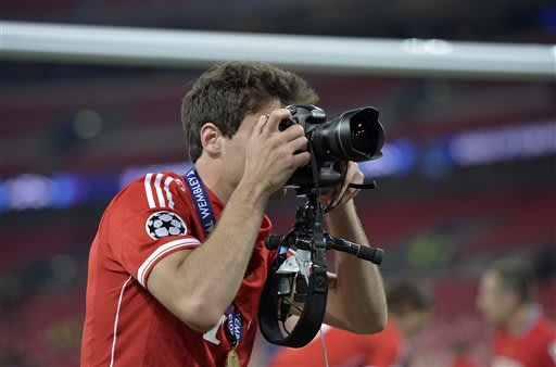 Bayern's Javi Martinez of Spain, takes a photo, after his team celebrate winning the Champions League Final soccer match against Borussia Dortmund,  at Wembley Stadium in London, Saturday May 25, 2013