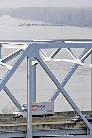 IDENTIFIES IN THE BRIDGE IN PHOTO AND ADDS MORE DETAILS ON INCIDENT -The towboat Nature Way Endeavor banks a barge against the western bank of the Mississippi River, Sunday, Jan. 27, 2013 as a vehicles travel on the Interstate 20 bridge. A barge carrying 80,000 gallons of oil hit the railroad bridge next to the I-20 bridge, spilling light crude into the Mississippi River and closing the waterway for eight miles in each direction, the Coast Guard said. A second barge was damaged. (AP Photo/Vicksburg Post, Eli Baylis)