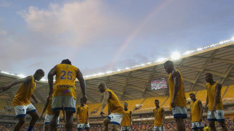 Players warm up in the Arena Amazonia Vivaldo Lima soccer stadium in Manaus