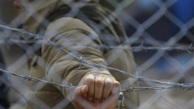 Migrant holds barbed wire fence at Macedonian-Greek border near Gevgelija