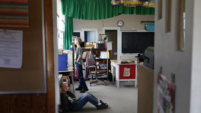 In this Tuesday, April 30, 2013, photo, Brandon Harrison, back, looks outside at Mount Baldy, as Tyrell Schrepfer waits to go outside for recess on in Polaris, Montana. The two students make up half the student population at Polaris School. (AP Photo/Kathryn Haake)