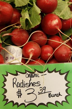 FILE - This March 16, 2011, file photo shows organic radishes at the Pacifica Farmers Market in Pacifica, Calif. Patient after patient asked: Is eating organic food, which costs more, really better for me? Unsure, Stanford University doctors dug through reams of research to find out _ and concluded there's little evidence that going organic is much healthier, citing only a few differences involving pesticides and antibiotics. Eating organic fruits and vegetables can lower exposure to pesticides, including for children _ but the amount measured from conventionally grown produce was within safety limits, the researchers reported Monday, Sept. 3, 2012. (AP Photo, File)